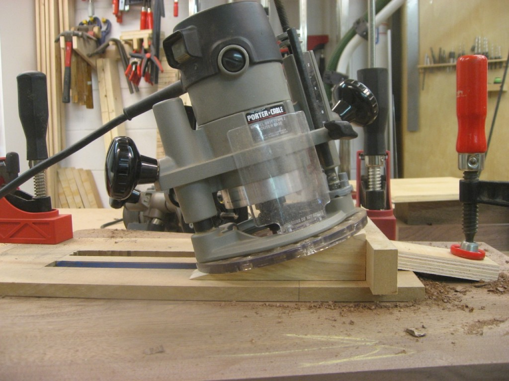 The router runs at an angle for the bit to remove waste at the bottom of the mortise