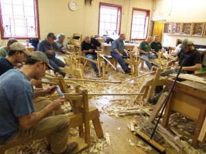 "Students are continuing their ride on the shave horses as they work to dimension and shape the 60"" long continuous arm of the chair."
