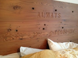The 2x12 redwood boards that made the rails of our pre-Katrina Animal General Hospital sign were planed, sanded and glued up to make this simple, rustic headboard. The engraved phrase came from a Delta Airlines SkyMall catalogue advertising a needlework project. I wrote down the expression while on a flight to see our grandchildren, and kept it tacked to the shop wall for years before finding the right place to use it.