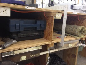 "Open shelves under what I call my ""saw table"" make it easy to see what's in place. Labels over each shelf make easy work of finding exactly the tool you want."