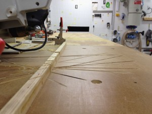 The bottom lines up with the top of the saw table.
