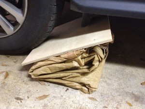 In our case, the garage floor is smooth enough that we didn't need a piece of plywood on the bottom. If I'd been doing this in the street, on asphalt, I would have used one to protect the tarp plastic from puncture damage.
